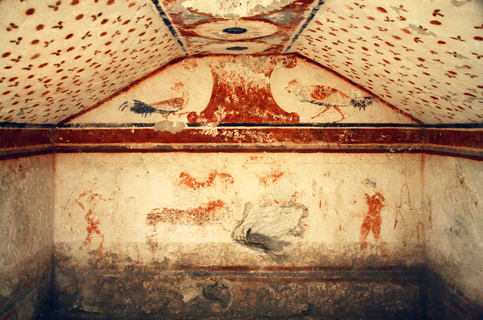 """Tomba dei Fiorellini"", 475-450 BC. You can see two red and black cockerels facing each other, ready to fight. Below them there is a banqueting couple."
