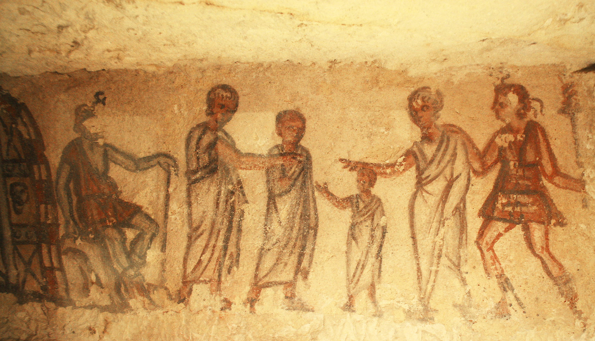 This scene shows a child in the middle, leading the newly deceased, who is followed by the Vanth-Etruscan female demon of the death. On the left you see the Hades' door among which Caronte is seated on the rock as a keeper-dead. Two members of the family, who are already dead, are receiving the newly deceased. (Tomba 5636)