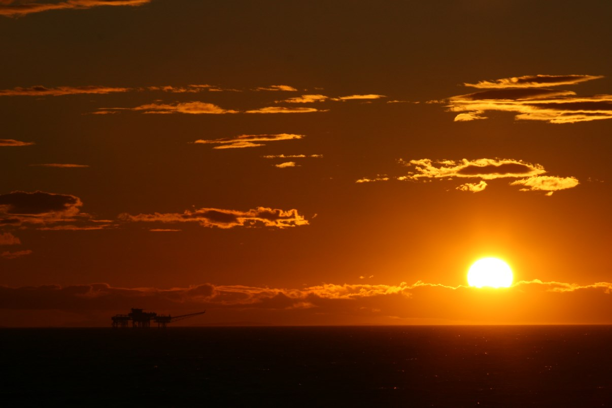 An oil platform under the setting sun.