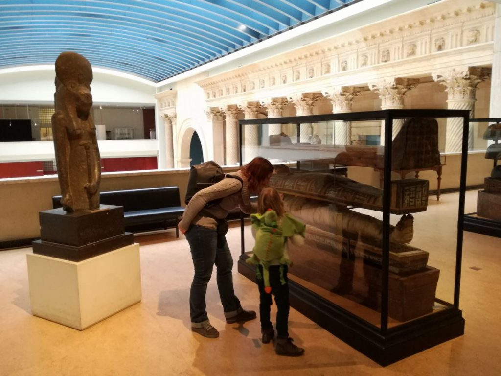 Mom showing Febe the interior of an Egyptian sarcophagus.