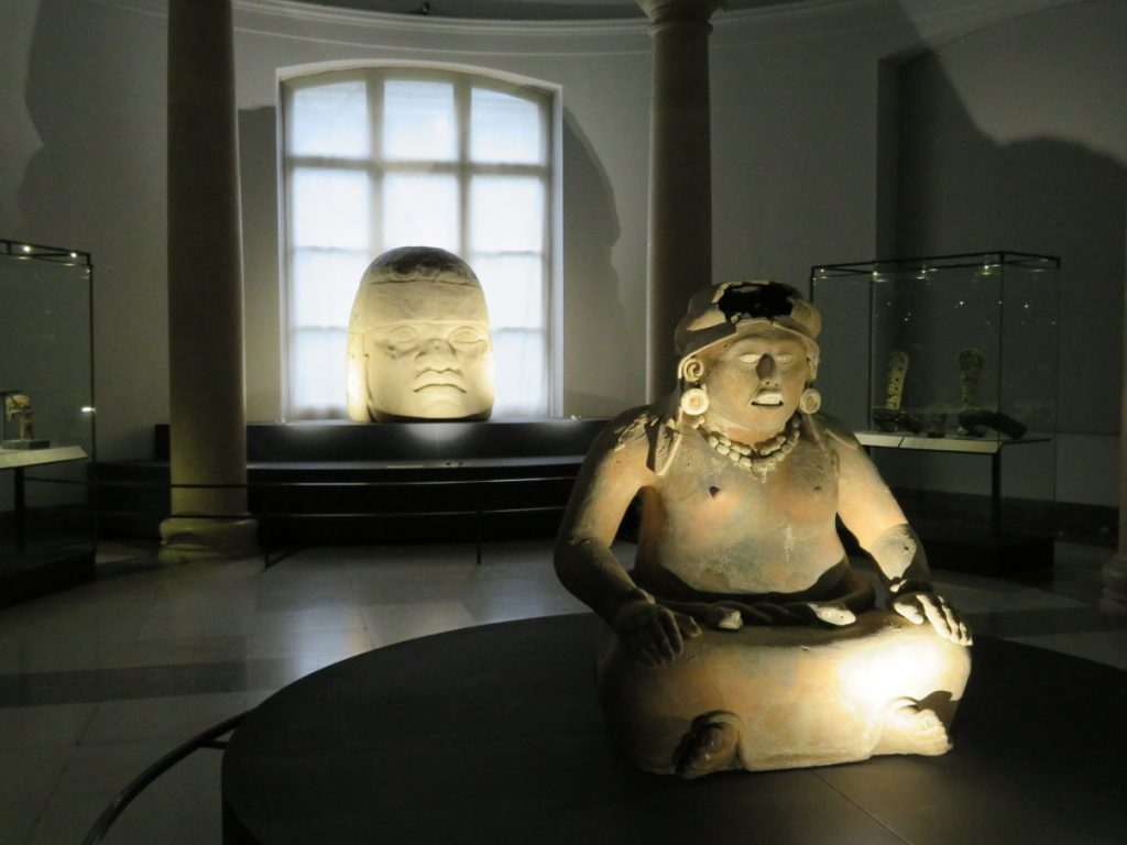 The Aztec fertility goddess Cihuacoatl, in front of an Olmec colossal stone head.