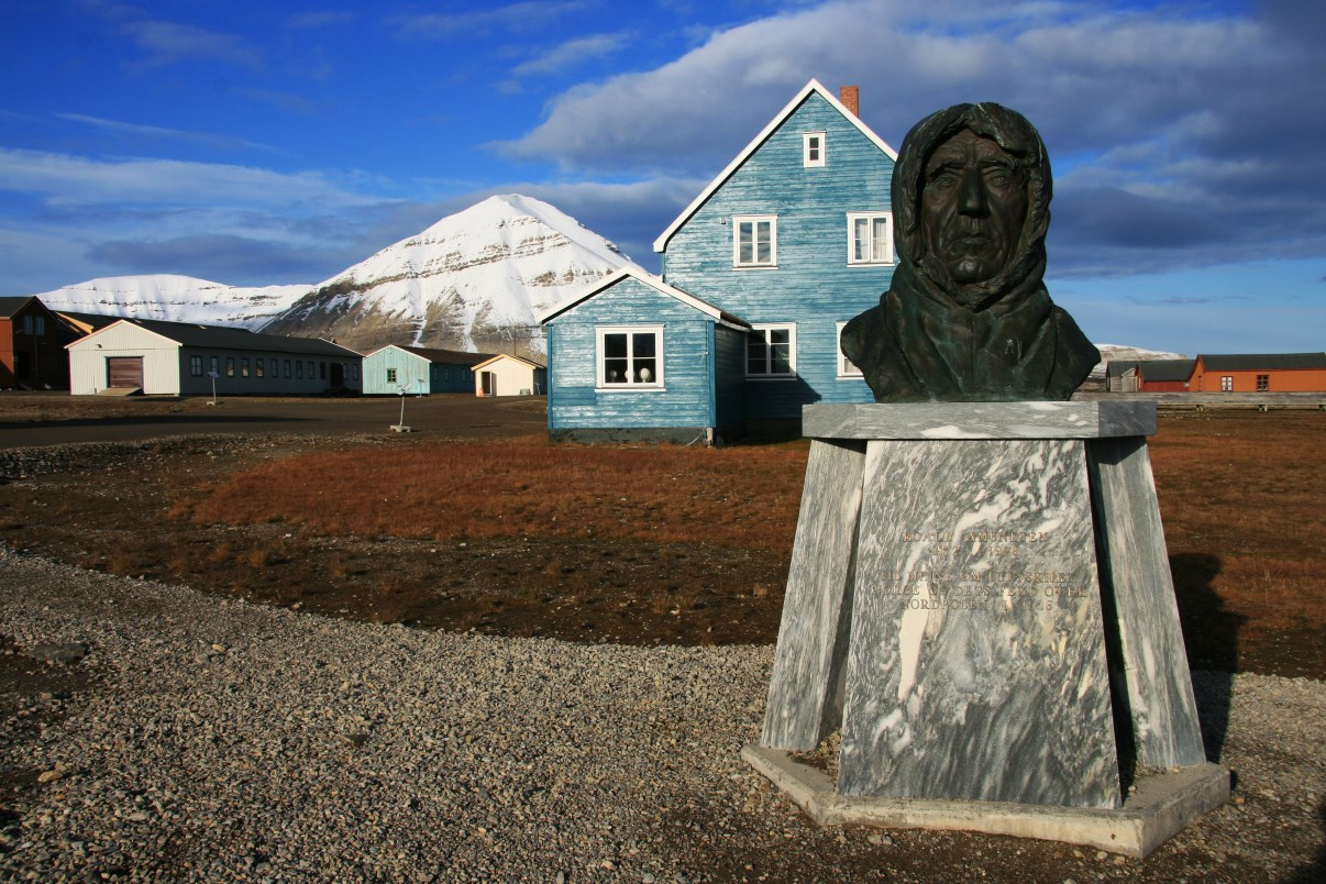 The blue house behind a bust of Norwegian polar explorer Roald Amundsen.