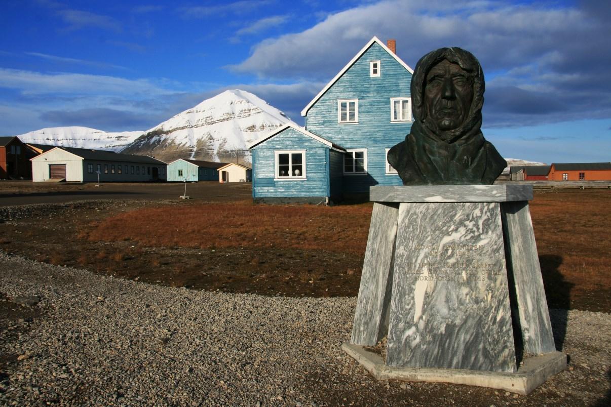 The blue house behind a bust of Norwegian polar explorer Roald Amundsen.